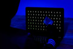 Hacker mit Kreditkarte Daten von einem Laptop in der Dunkelheit stehlend stockfotografie