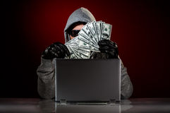 Hacker and money. Young hacker in a sunglasses with laptop and money in hand Stock Photos