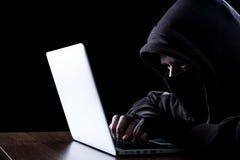 Hacker anônimo na obscuridade Fotos de Stock Royalty Free