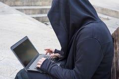 Hacker novo perigoso que quebra um código secreto com seu portátil que senta-se em um banco fora Foto de Stock Royalty Free