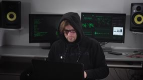 Hacker offender carries out clandestine cyber attacks with the use of a laptop with special software in a secret office. In the background are two monitor stock footage