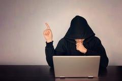 Hacker okapturzający przed jego komputerowego przedstawienia palcem ciemną twarz kapturzasty technologii pojęcie, hackerów punkty zdjęcie royalty free