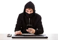 Hacker with a Phone. Surprised Hacker with a Mobile Phone and the Computer Keyboard on the White Background stock photos