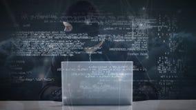 Hacker pisać na maszynie na laptopie w masce narciarskiej podczas gdy patrzejący wokoło nerwowo