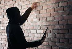 Hacker pracuje na jego komputerze Czerń zamaskowany hacker w czerni fotografia royalty free