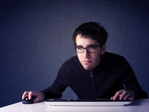 Hacker pracuje z klawiaturą na błękitnym tle Fotografia Stock