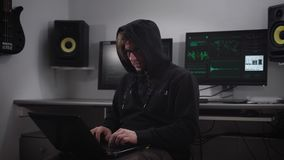 A hacker is preparing for cyber-attack in the underground computer room. A man at a rapid pace enters the information on stock video
