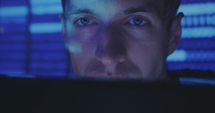 Close up face of Hacker programmer is working on computer writing the code in cyber security center. Hacker programmer in glasses is working on computer while stock video footage