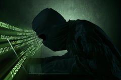 Hacker que datilografa em um portátil Imagens de Stock
