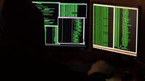 Hacker que quebra o código Hacker criminoso com sistema de rede penetrante da capa preta de sua sala escura do hacker video estoque