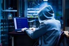 Hacker que tentam esconder na obscuridade imagem de stock