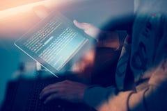 Hacker que usa o computador, o smartphone e a codificação para roubar a senha a fotos de stock