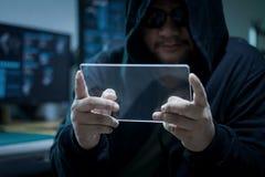Hacker que usa a tabuleta de vidro clara vazia com obscuridade azul e grão p Foto de Stock