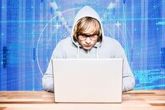 Hacker que usa um portátil com um fundo digital azul foto de stock royalty free