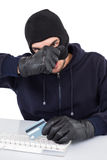 Hacker removing his balaclava to show his face Royalty Free Stock Photography