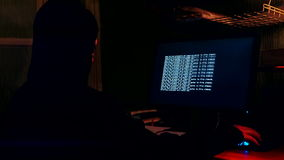 Hacker in the room in front of a computer monitor stock footage
