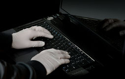 Hacker's hand on laptop Stock Photography