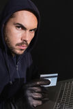 Hacker shopping online with laptop Stock Images