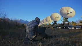Hacker sieka radiowego teleskop używać notatnika Mężczyzna programować siekać na laptopie w naturze Terrorysta chuje wewnątrz zbiory