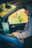 Hacker sit in car with his laptop Stock Images