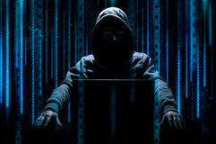 Hacker sits behind laptop Stock Photos