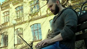 The hacker sits in the park and typing program stock video