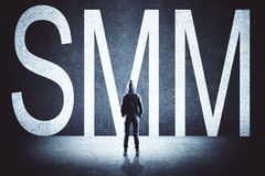 Hacker with SMM. Hacker with creative SMM text on concrete background. Social media and communication concept stock photography