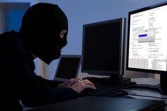 Hacker som nedladdar information av en dator Arkivbild