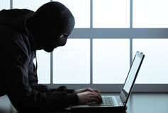 Hacker stealing data. Computer hacker - Male thief stealing data from laptop Stock Photography