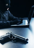 Hacker stealing data. Computer hacker - Male thief stealing data from laptop, focus on gun Stock Photography