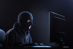 Hacker stealing data. Computer hacker - Male thief stealing data from computer Stock Images
