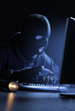 Hacker stealing data. Computer hacker - Male thief stealing data from computer Royalty Free Stock Image