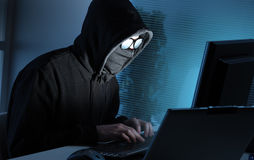 Hacker stealing data from computer. Young male thief stealing data from computer Royalty Free Stock Photo
