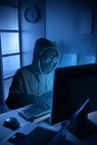 Hacker stealing data from computer. Young male thief stealing data from computer Royalty Free Stock Photography