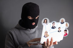 Hacker stealing data from internet over grey Stock Photography