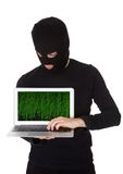 Hacker stealing data from a laptop. Hacker dressed in black with a mask standing stealing data from a laptop with the screen pointed towards the camera in a Stock Photos