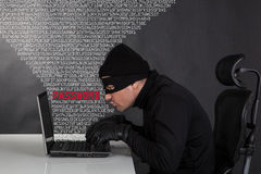 Hacker stealing data. From a laptop on black background stock photography