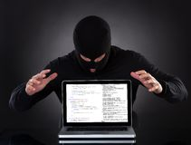 Hacker stealing data of a laptop computer. Hacker in a balaclava standing in the darkness furtively stealing data off a laptop computer or inserting spyware in royalty free stock photos