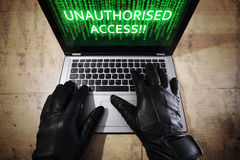 Hacker stealing data from a laptop Royalty Free Stock Images
