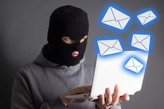 Hacker stealing data from laptop or sending spam messages. Hacker in mask stealing data from laptop or sending spam messages Royalty Free Stock Photos