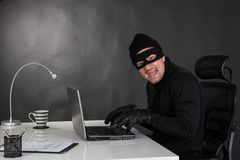 Hacker stealing data and laughing Stock Images