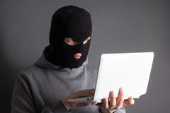 Hacker stealing data from laptop over grey Royalty Free Stock Photo