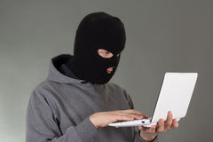 Hacker stealing data from white laptop. Hacker stealing data from white notebook Royalty Free Stock Images