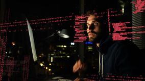 Hacker stealing information. Side view of a sneaky hacker working on a computer while digital effects of interface codes are running in the foreground stock footage