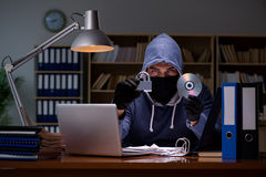 The hacker stealing personal data from home computer. Hacker stealing personal data from home computer Royalty Free Stock Images