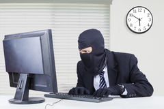 Hacker steals data on computer. Male hacker wearing mask and steal data on the computer while typing on the keyboard and looking at the monitor Stock Photos