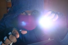 Hacker with torch stealing information- data theft idea Royalty Free Stock Image