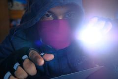 Hacker with torch stealing information- data theft idea.  Royalty Free Stock Photography