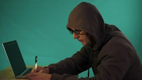 Hacker typing code. Green type on screen. Night and low key. Close-up. Indoors night work. Programmer coding software of. Site. A hacker is preparing an attack stock video footage