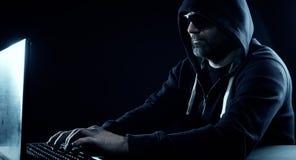 Hacker typing on computer keyboard black background Royalty Free Stock Image